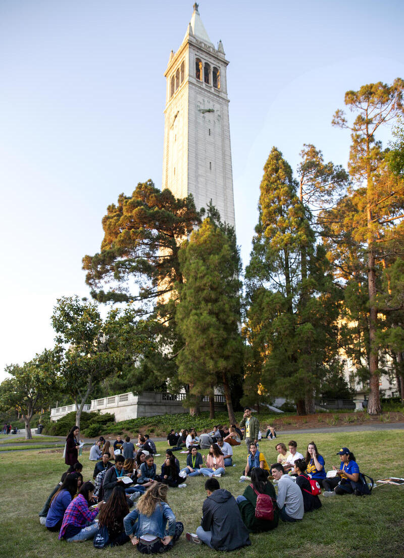 Group of students sitting in a circle in front of Bell tower