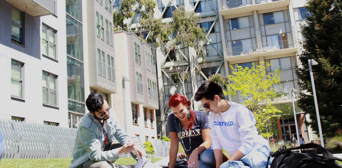 Three students outside reading