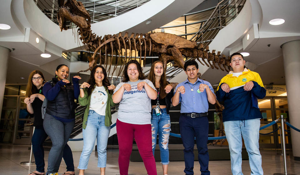 Group of students posing in front of T-Rex